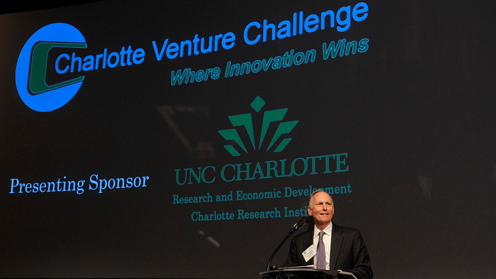 Man standing at podium announcing 2014 Charlotte Venture Challenge winner