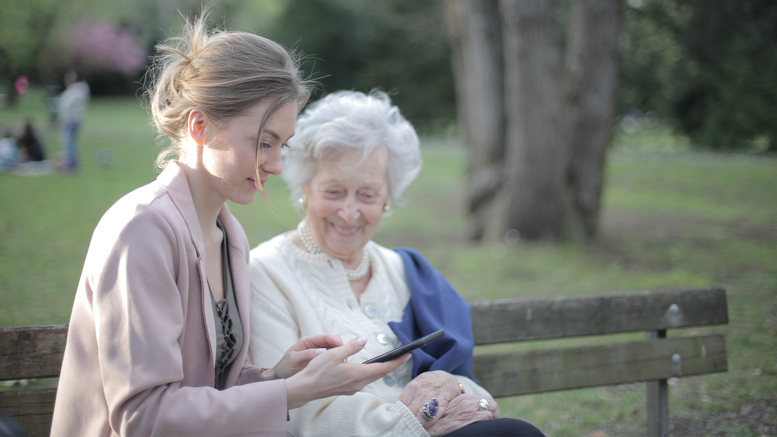 woman showing her elderly mother something on her phone, explaining intelligent digital assistants